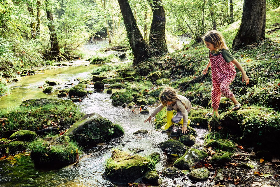 Two children playing near a stream